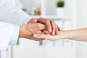 Friendly male doctor's hands holding female patient's hand for encouragement and empathy. Partnership trust and medical ethics concept. Bad news lessening and support. Patient cheering and support